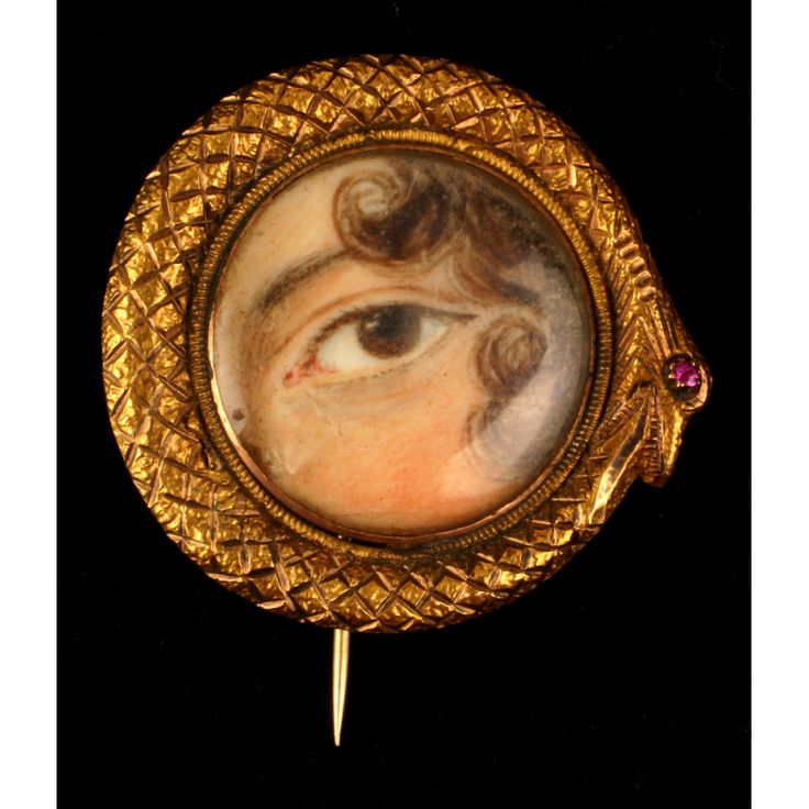 """Mourning Brooch (""""Tear"""" jewelry), 1800-1830. Made from Ivory, paint, metal, garnet, and glass. 1 x 1 in. Brooch of the mourning """"Tear"""" jewelry type; detail of 1 brown eye and side of face with curling hair; etched frame in gold metal designed as snake swallowing its own tail and with 1 pink garnet eye; glass on obverse is chipped; glass compartment on reverse meant to hold hair (now empty); pin attachment. From the New York Historical Society."""