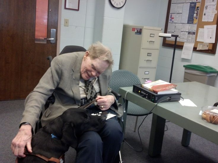 Photo of Rev. George S. McDermott with his Seeing Eye dog, Kernel, in the faculty lounge at Quinsigamond Community College where he taught for more than 20 years