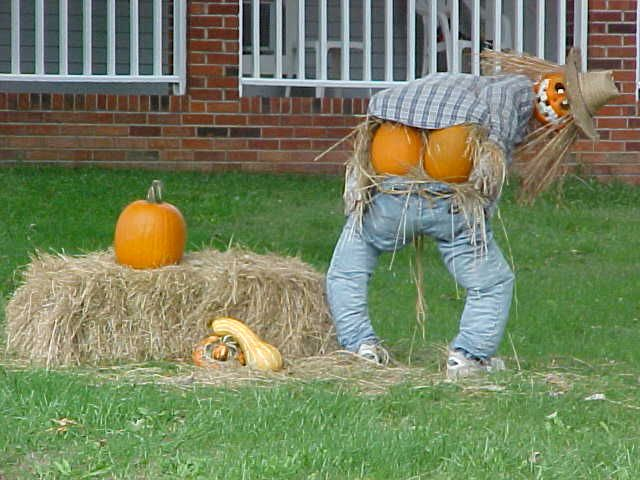 A homemade scarecrow dressed like a pumpkin flasher next to a straw bale.
