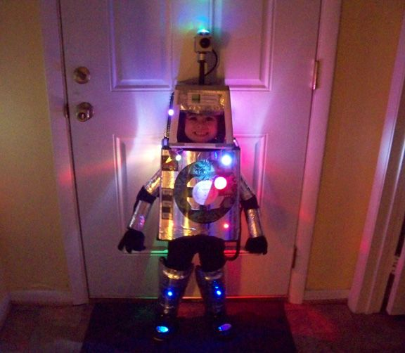 Little gal in her DIY LED robot costume - good job, parents. Re-create something similar for Halloween with these lil' LED lights: http://www.flashingblinkylights.com/light-up-products/light-up-flashing-pins-body-lights/blinkies-round-leds.html