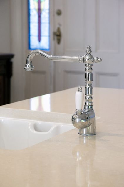 Fixtures  Farmhouse sinks add a feeling of nostalgia to a kitchen and bring a sense of rustic character that enhances country- and traditional-style kitchens. Complete the look by pairing your white porcelain farmhouse sink with a beautiful traditional-style tap, many of which are available with matching white porcelain handles, as shown here. Typical farmhouse sinks do not have a hole for the faucet, so the tap needs to be positioned in the counter or in the wall behind.