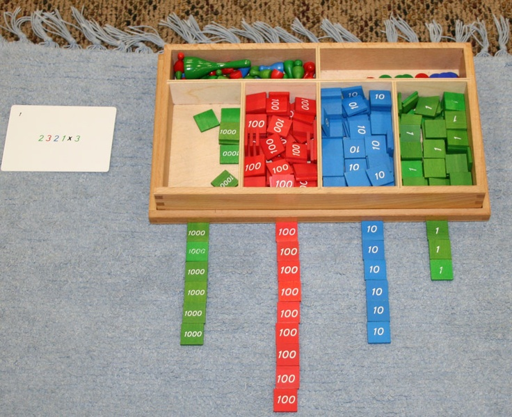 Another view of Stamp Game. The child is using it to multiply. This problem needs no regrouping, but if it did, she would trade tiles to arrive at the product.
