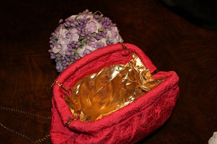 orange silk bag embroidered with gold leather lining. Gold chain and silk
