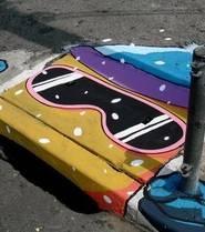 Cette oeuvre Street Art représente un skieur dessiné à partir de la forme d'une bouche d'égout