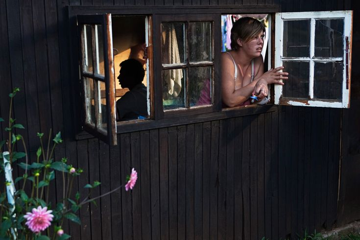 A woman looks out the window of her one-room hut at a squatter camp for poor white South Africans at Coronation Park in Krugersdorp, South Africa on March 9, 2010. (REUTERS/Finbarr O'Reilly)