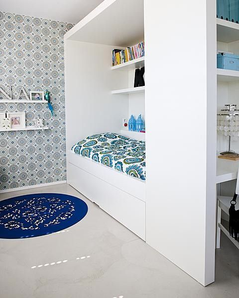 The built-in surroundings for the bed in this child's bedroom extend to the ceiling to create lots of storage space.