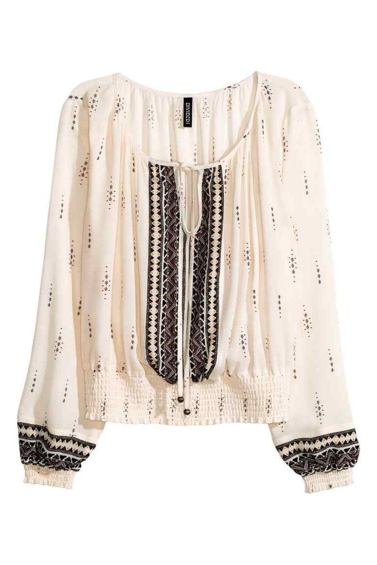 Blouse bohème: Blouse en tissu à motif imprimé. Encolure large avec liens à nouer terminés par perles fantaisie aux extrémités. Smocks en bas de manche et à la base.