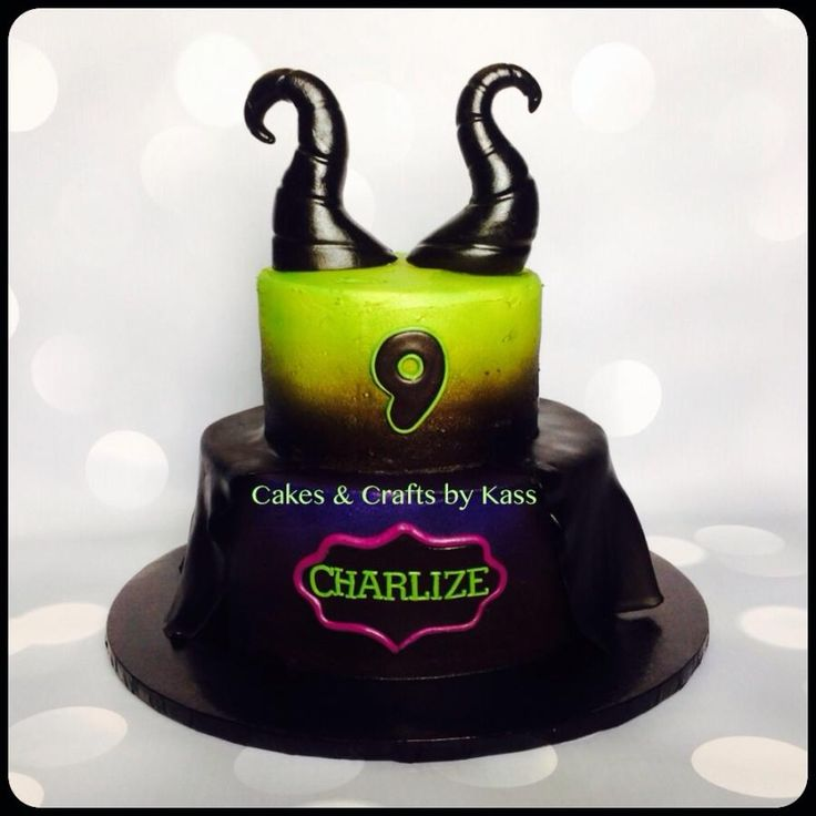 """Magnificent Malificent  8"""" tier airbrushed in black and purple then added a fondant """"cape"""". Fondant name plaque done in purple,electric green and black. 6"""" cake airbrushed in electric green and black. Horns are solid gumpaste and airbrushed in black."""