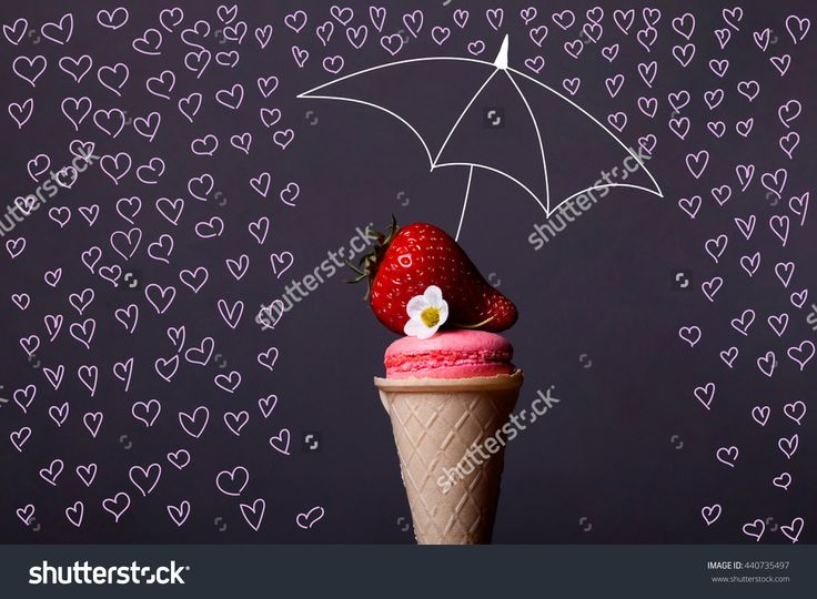 Colorful macaron pink color in ice cream cone of waffle on grey background with strawberry and flower and umbrella with heart raindrops, copy space, overlay image