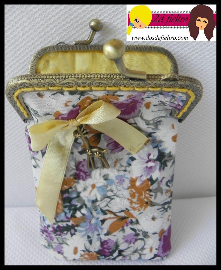 monedero boquilla metalica cuadrada con tela exterior de flores en tonos blancos, naranjas y rosas. tela interior amarilla con flores. Lazo amarillo con colgante jirafa