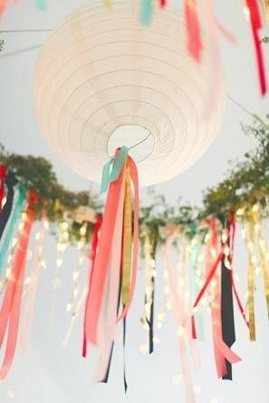 Large white paper lantern decorations hang in center of ivy and ribbon faux chandelier at a tented wedding venue.