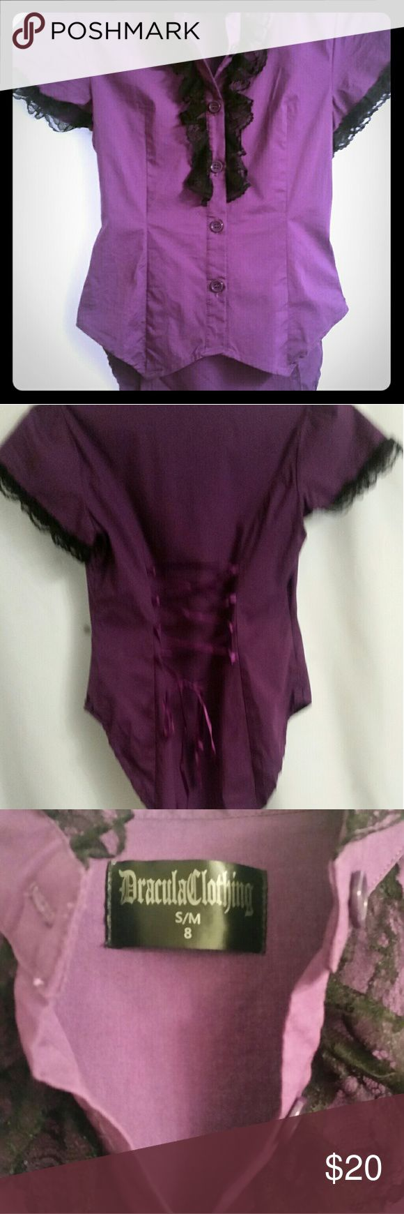 Purple corset laced blouse Purple short sleeve with black lace ruffle detail. Back is laced up corset style with slightly longer back/tail. European cut so it says small/mediuim. I would say it fits like a 4. Dracula clothing Tops Button Down Shirts