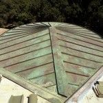 Standing seam copper roof with front tapered panel section. Green over brown patina