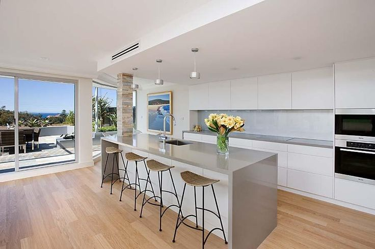 Square set dropped ceiling with pendants an, concealed range hood and caesarstone benchtop similar colour to Raw Cement.