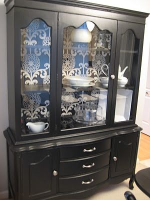I did this same thing once to a china hutch...my Mom is still angry with me for giving it away!  I'm thinking about putting fabric or painting the backs of some of my kitchen cabinets...just need to find the right pattern!
