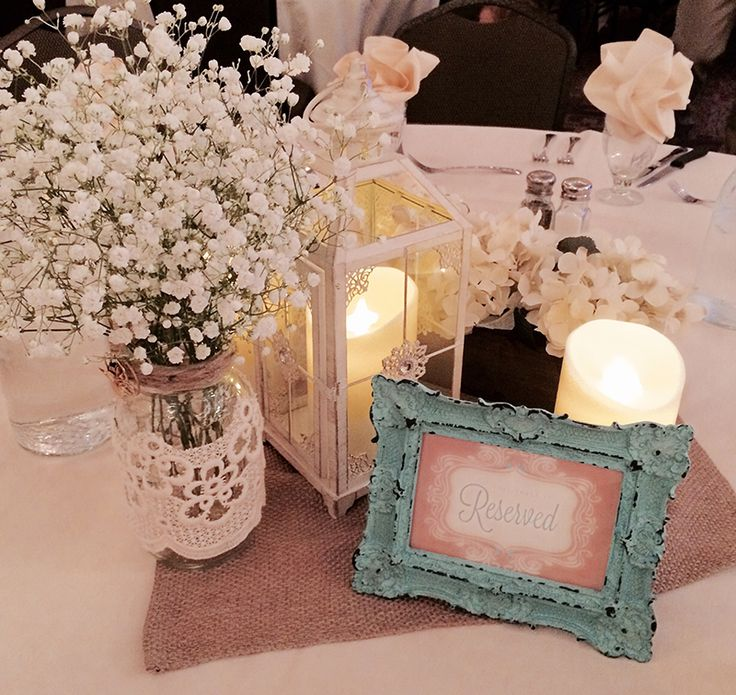 Fresh Baby's Breath in mason jar wrapped in lace. Ivory lantern, flameless candles, and burlap square. Coral reserved sign in teal vintage frame. By Hitch Studio, Brookings, SD.