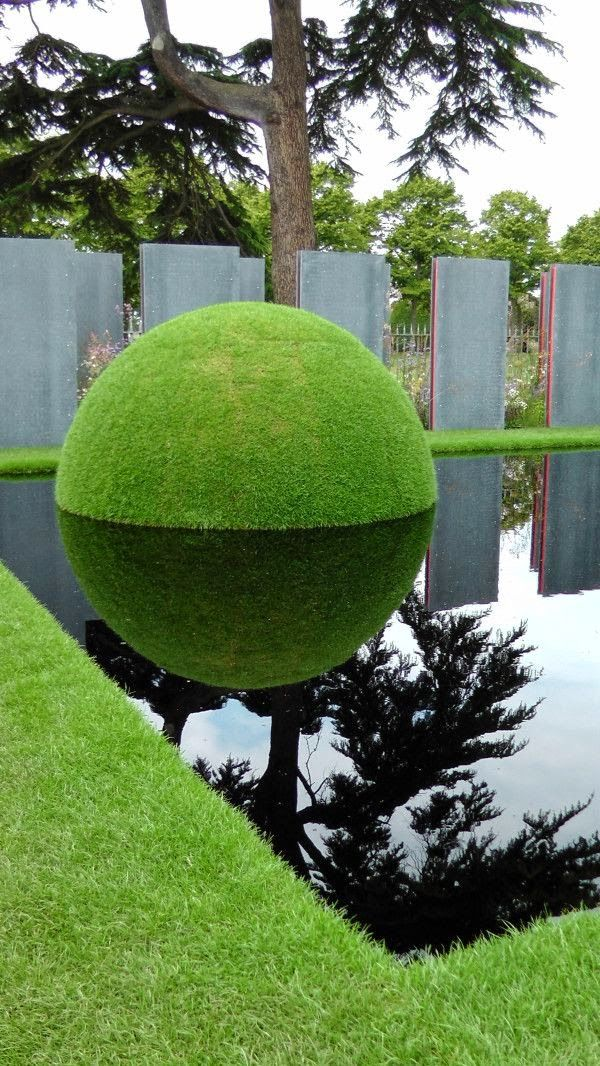 Green sphere reflecting on the water, part of the World Vision Garden at the Hampton Court Flower Show in 2013 #topiary #landscaping #formalgarden #labyrinth #boxwood - More wonders at www.francescocatalano.it