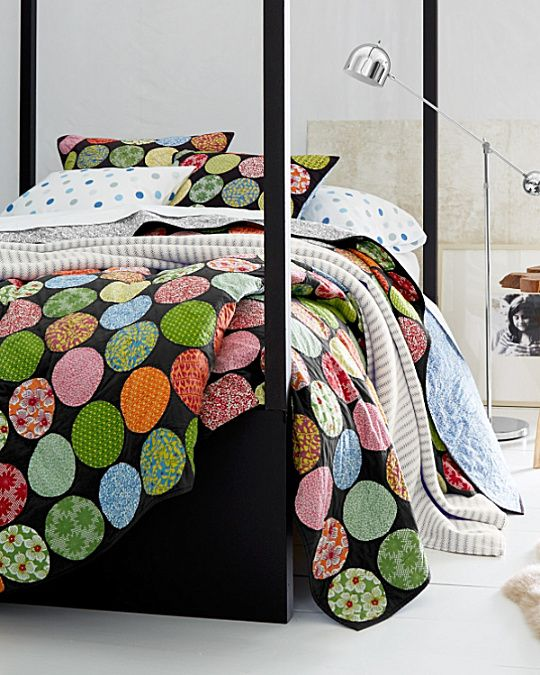 Now offered with a light and bright ground our popular hand-stitched quilt sets the trend with lively circular patches of retro prints.