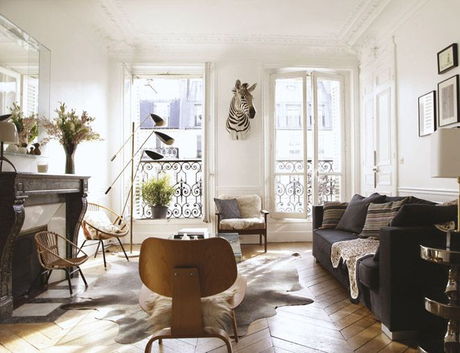 Home of Cécile Roederer, founder of Smallable. Photo: ELLE Decor España.  White walls, earth tones, herring bone wood floor, fireplace, dark grey couch, bohemian chic interior.