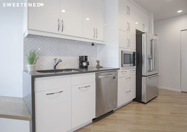 Midtown kitchen features glossy white IKEA Sektion cabinets and marble backsplash tiles with herringbone pattern from Complete Tile.