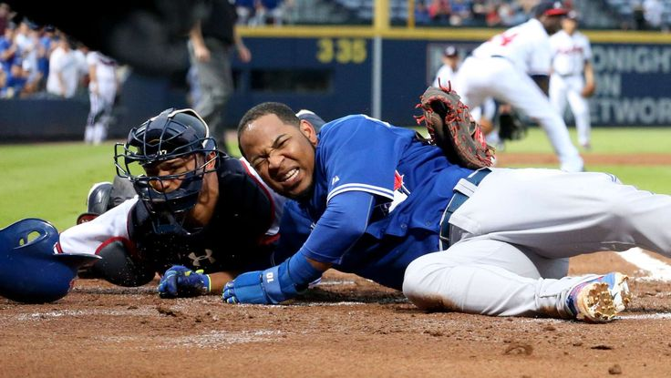 Beating the throw -  Toronto Blue Jays first baseman Edwin Encarnacion collides with Atlanta Braves catcher Christian Bethancourt as he scores in the first inning on Sept. 16. The Blue Jays won 9-1. - © Jason Getz/USA TODAY Sports