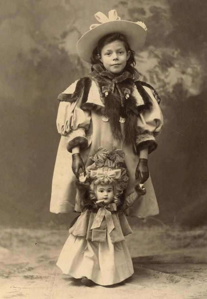 Opulent girl from the 1894-1897 holding her charming German dolly face doll dressed in the very same style.