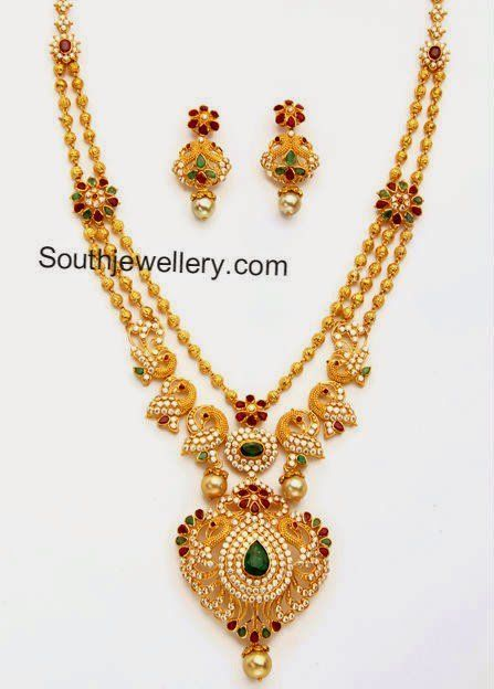 22 carat gold beautiful peacock design gundla haram studded with cubic zircons, rubies, emeralds and south sea pearl drops. weight: 69 grams Price: Approx Rs. 2,34,000 (BUY HERE) Related PostsPeacock Mango Pacchi Haram and JhumkasPeacock CZ Pacchi NecklaceGundla Haram with Peacock PendantGold Haram with CZ Stones PendantDiamond Pendant and Jhumkas SetCZ Peacock Mango Long Necklace