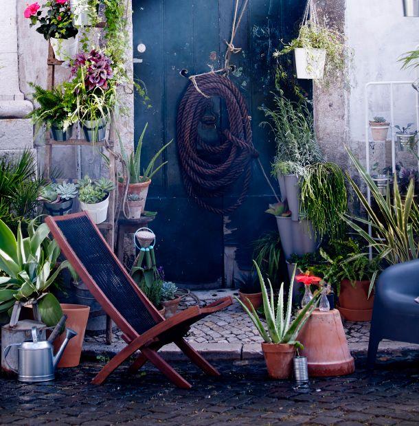 Gartenambiente mit einigen verschiedenen Übertöpfen, u. a. mit BROMMÖ Ruhesessel für draußen in Schwarz/Braun