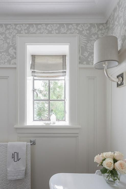 grey and white bathroom with tiny round vase of ivory roses