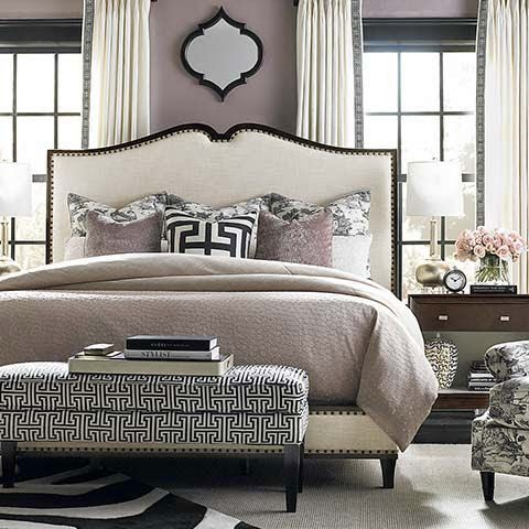 Comforting neutral bedroom with bed flanked by two windows and a Greek key accent pillow