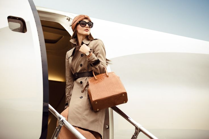 Private Jet Fashion Spread - Billionaire Cotton gabardine trench coat with leather belt and epaulets, Burberry London; pleated dress in double-face linen, and calfskin and cashmere headband, both Hermès; sunglasses, Giorgio Armani; Sambre crocodile handbag, Bally; Arceau Ecuyère timepiece with silvered dial in a rose gold case set with diamonds and matt havana alligator strap, Hermès. Executive jet, Embraer Lineage 1000E.