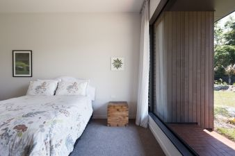 A large floor to ceiling window keeps this bedroom feeling open