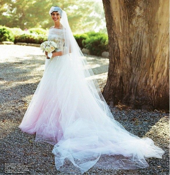 Anne Hathaway Wedding Valentino -  November 2012 - custom design created by legendary couturier Valentino Garavani. The strapless gown was breathtaking: painstakingly crafted from ivory silk and d'esprit tulle by seamstresses in Valentino's Rome atelier. The train was hand-painted with shades of pink and embroidered with satin flowers. A 1920s-inspired veil topped off the look, which featured a large flower covered in crystal beads.