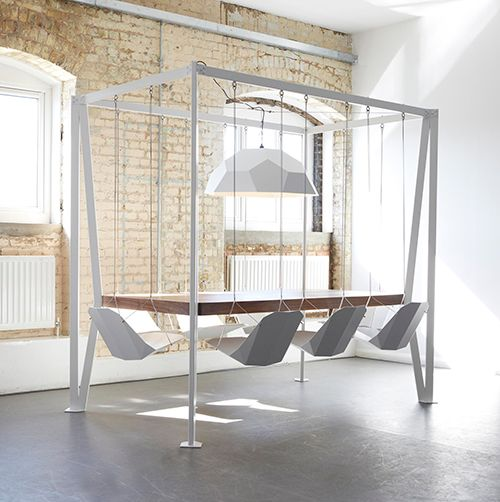 A table with 8 hanging chairs and a suspended lamp by Duffy London