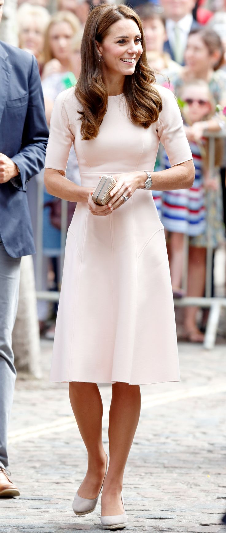 Kate Middleton was pretty in pink for a royal visit to Cornwall, where she and Prince William took the day for a series of engagements at local youth organizations in the coastal county. Middleton looked radiant in a pale pink fit-and-flare dress by Lela Rose and a summery pair of Monsoon espadrille wedges, wearing her hair in loose, effortless waves and kept her makeup on the natural side.