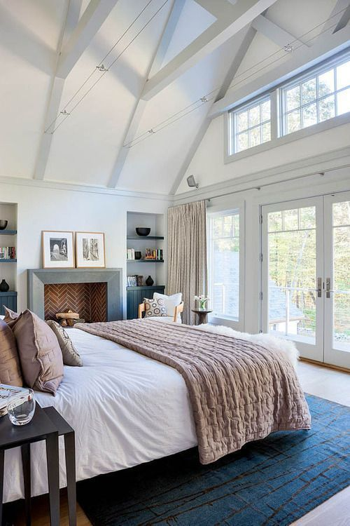 Bedroom decor ideas - light and bright bedroom with open beam ceiling, fireplace, neutral bedding.
