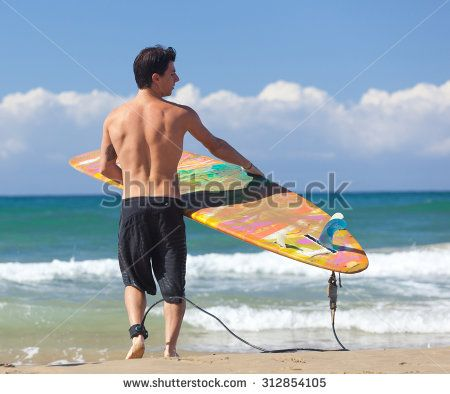 Portrait of Surfer with longboard on the beach.