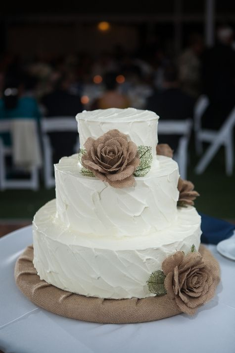 Three tiered white wedding cake with burlap flowers // Cake: A Spoon Fulla Sugar // Shelby Street Photography // http://www.theknot.com/submit-your-wedding/photo/a3e9e9eb-ee4d-41c6-9c0a-c56f38f4bcfe/Volk-Wedding