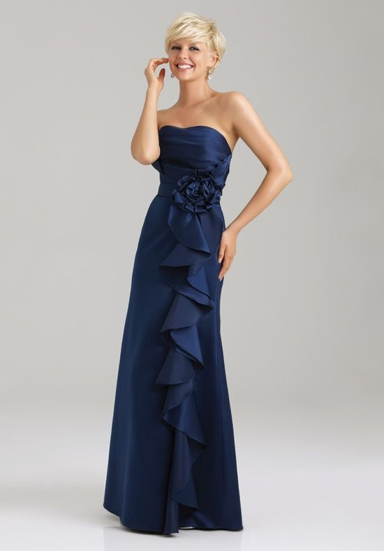 This long satin gown features a crumb-cather  bodice with a floral accent and cascading ruffles along the A-line silhouette.