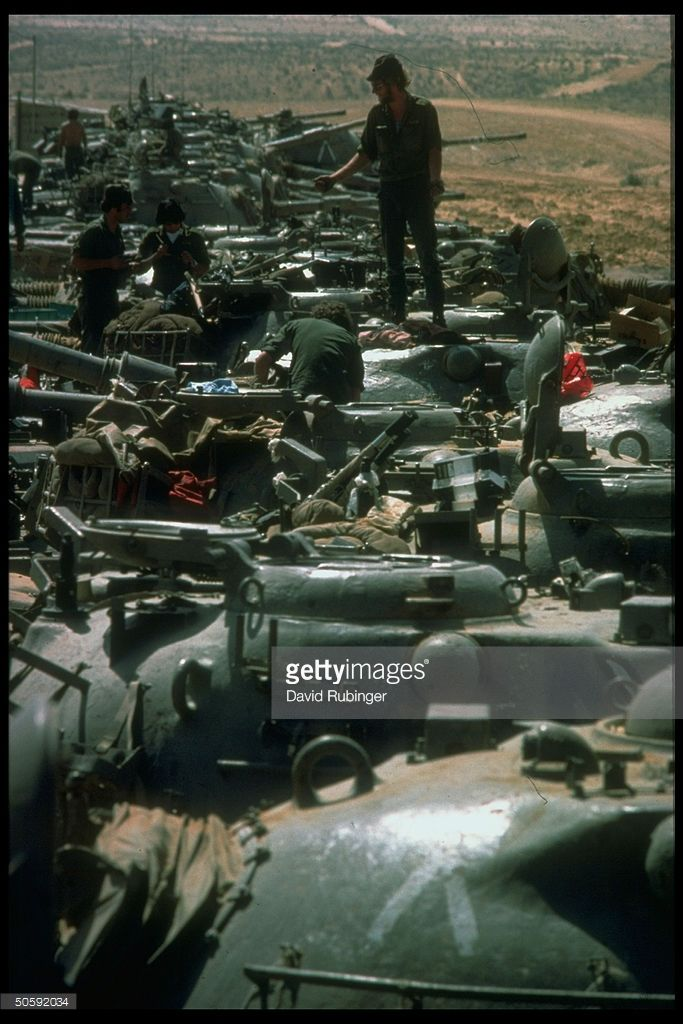 Israeli tank crews working atop line of parked tanks, during Peace for Galilee invasion.