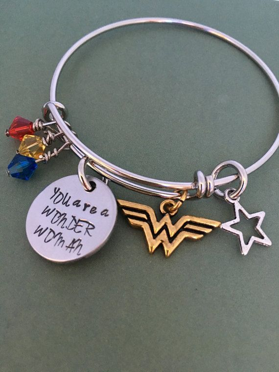 Give the wonder woman in your life a gift of love and remind her how important she is to you with this adjustable bracelet complete hand-stamped, 2-sided charm, star charm, Wonder Woman charm, and three jewels in red, yellow and blue. Bracelet is adjustable - 6-8 inches. The bracelet is made out of copper with Rhodium plating, which gives it the silver shine. The circle charm is aluminum. The jump rings and charms are base metal. The bracelet comes ready to give, packaged in a hand-stamped…