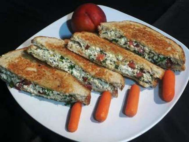 Paneer Sandwich Recipe 100 gms paneer (cottage cheese) crumbled or grated 8 fresh bread slices (brown or white) 1 small onion finely chopped 4 green chillies chopped 4 cloves garlic crushed 1 tomato cut into slices 1 small capsicum cut into rings 1/2 tsp red chilli powder 1/2 tsp cumin powder 1/4 tsp amchur powder 1 tbsp coriander chutney 1 tbsp butter 1 tsp oil Fresh coriander leaves Salt to taste