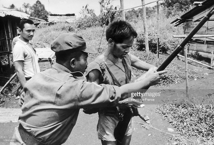 An Indonesian Officer Showing A Dayak How To Hold A Shotgun During A Hunt For Guerrilla Communists In Borneo, On December 5Th 1968.