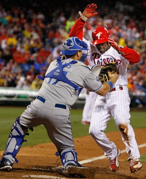 Phillies shortstop Jimmy Rollins gets tagged out by Dodgers catcher A.J. Elis after a fielder