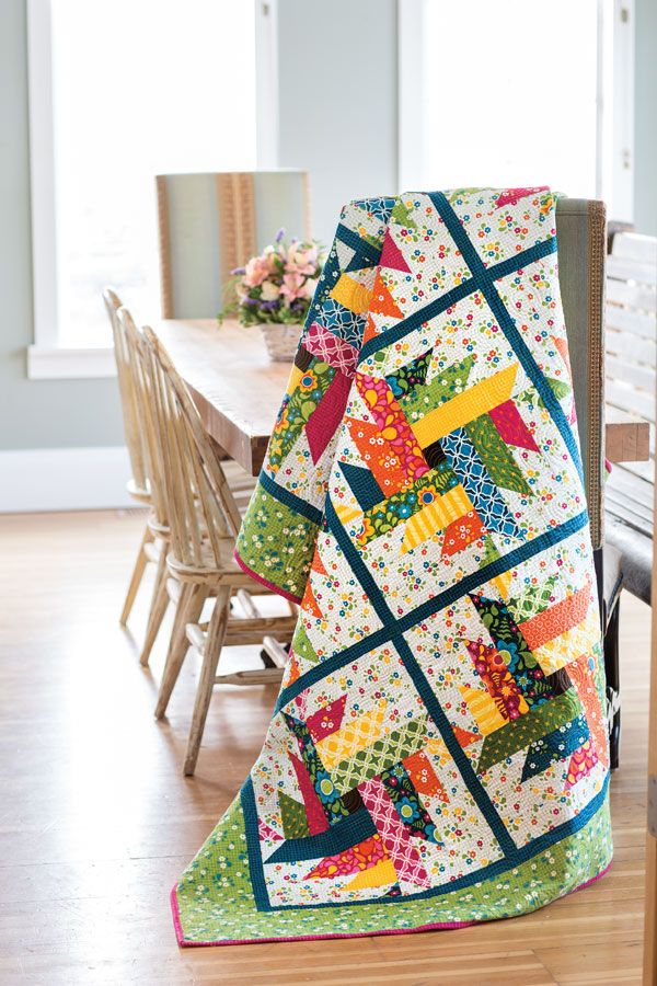 """This is a fun quilt to make use of bright printed 10"""" squares. Designer Emily Bailey came up with the setting when playing with a variation of Delectable Mountain quilt blocks. Look for scrappy quilt patterns like Twisted Posies in Scrap Quilts Spring '15."""