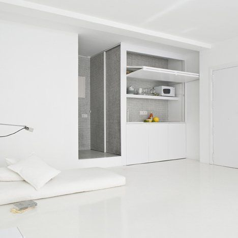 Seaside studio apartment in Barcelona by Colombo and Serboli Architecture with an all-white interior that includes a tiled kitchen and bathroom.