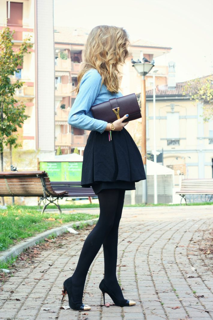 The typical black skirt, black tights and black courts style can seem boring, but the look can be updated with gold tipped toes and an interesting structure to your bottom half. Opt for a coloured shirt instead of white to freshen up the look.