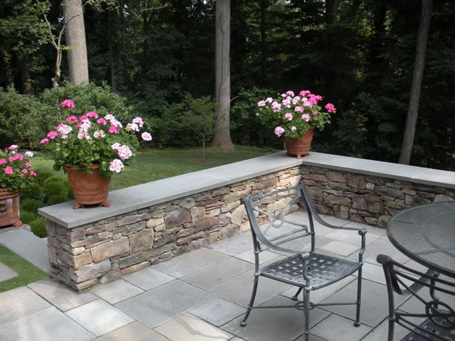 Retaining wall, bluestone capped seating wall was created using natural fieldstone to give the appearance of a stone stacked wall that was built long ago.