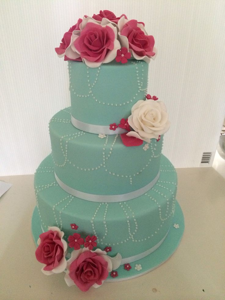 3 tiered teal colour cake with dotted draping and roses