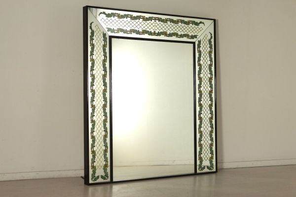 Specchiera Brusotti di grandi dimensioni montata su telaio in legno; specchio decorato predisposto alla retro illuminazione. Buone condizioni, presenta piccoli segni di usura. Originariamente comprende una base su cui appoggia a finto camino come da foto.